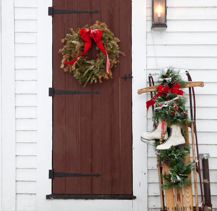 An antique door decorated for Christmas with freshly fallen snow outside.