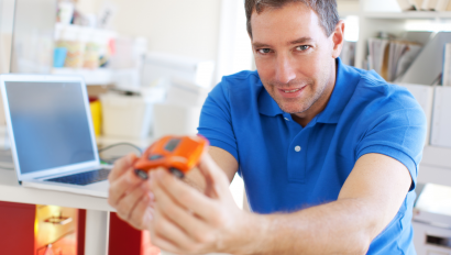 A man holding an orange toy car.