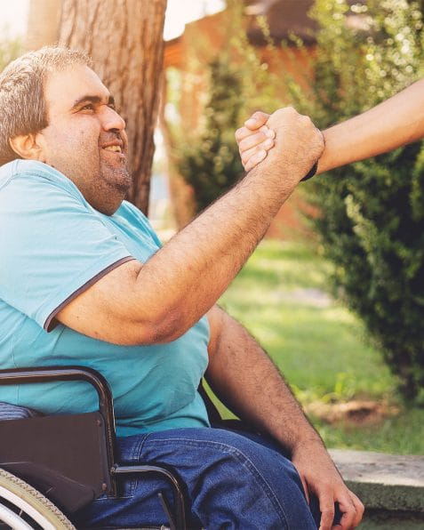 A man on a wheelchair, grabbing another person's hand.