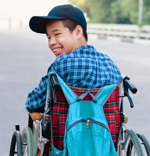 A young boy on a wheelchair, looking back and smiling.