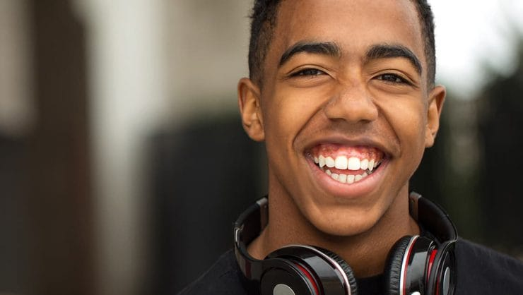 A young man with headphones around his neck, smiling.