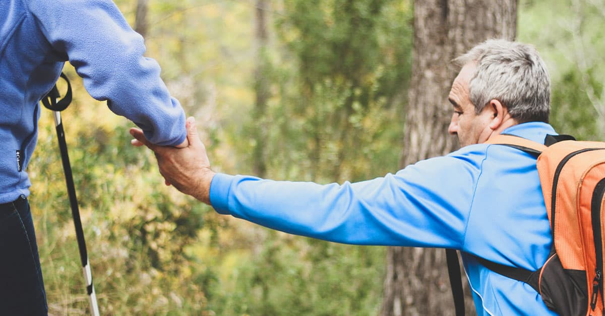 A person helping a man hiking by grabbing his hand.