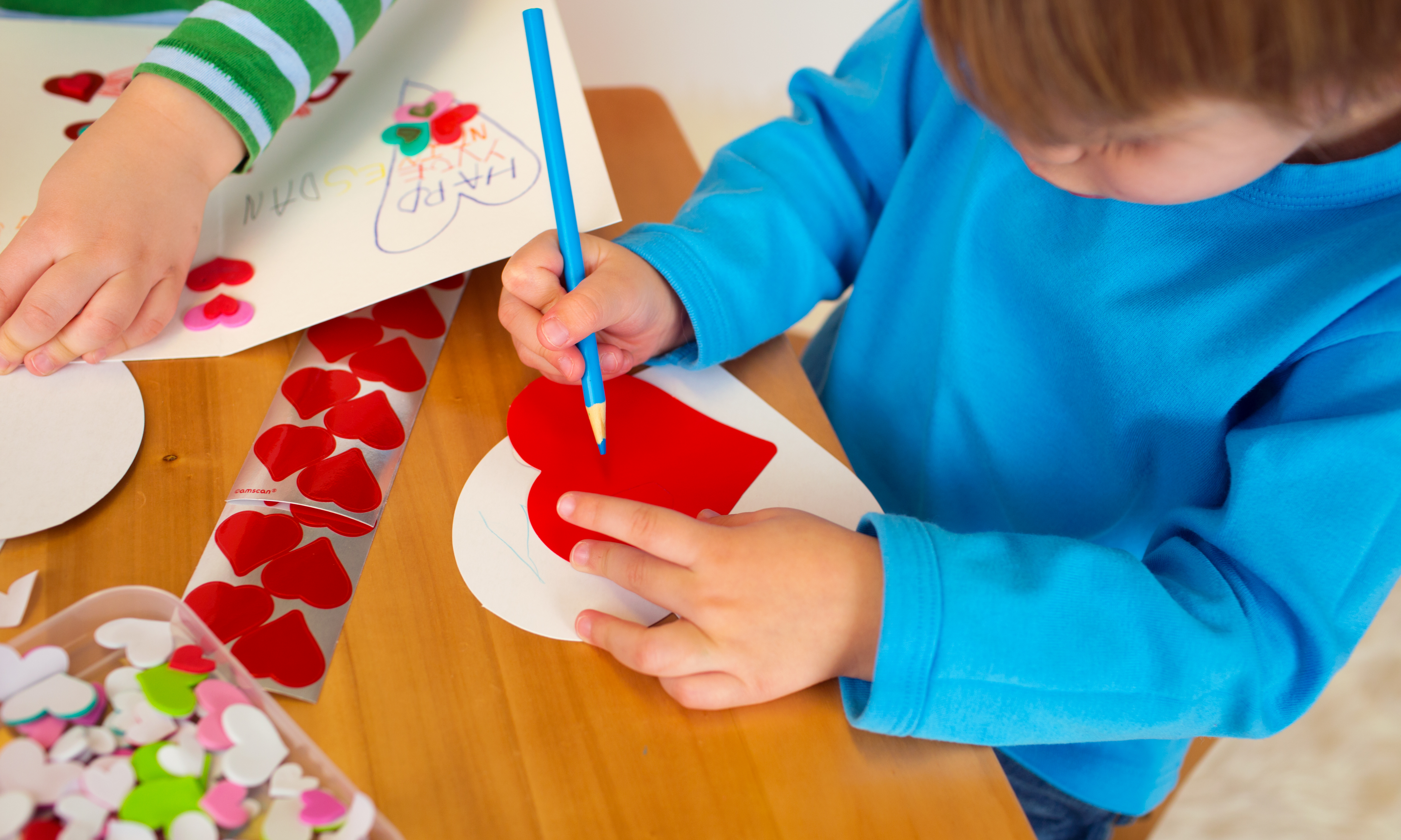 A child holding a blue colored pencil and a paper heart.
