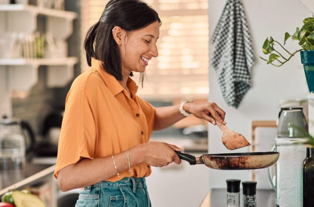 Shot of a happy young woman preparing a healthy meal at home.