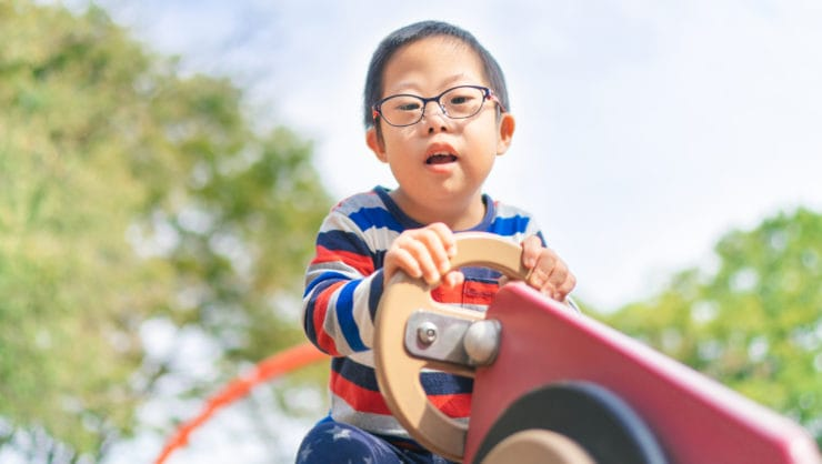 A small child with down syndrome is playing on a seesaw in a playground on a sunny day.