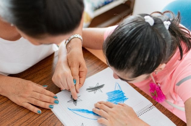 A young girl coloring with a caregiver.