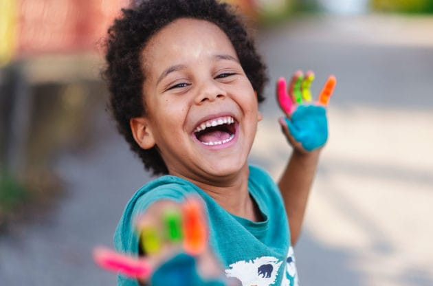 A boy laughing with colorful paint on his hands.