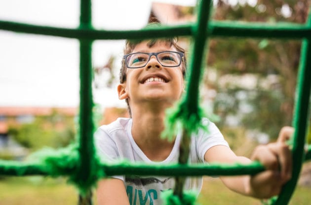 A boy climbing up a rope ladder on a playground.