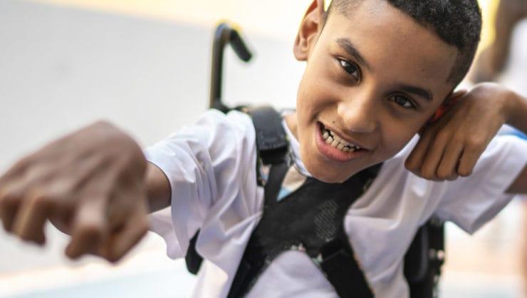 A boy smiling in a wheelchair.