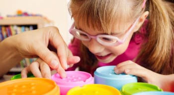 A little girl with glasses playing with colorful disks.