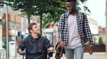 A young man walking besides a person in a wheelchair.