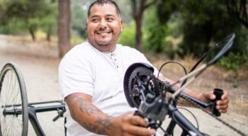 A man sitting in a bicycle used by people with physical disabilities.