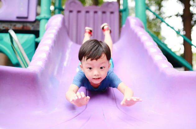 A little boy sliding down the slide.