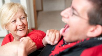 A woman sitting with a young man in a wheel chair with developmental disabilities.