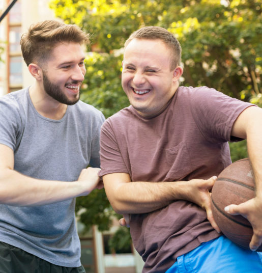 Two young men smiling playing basketball.